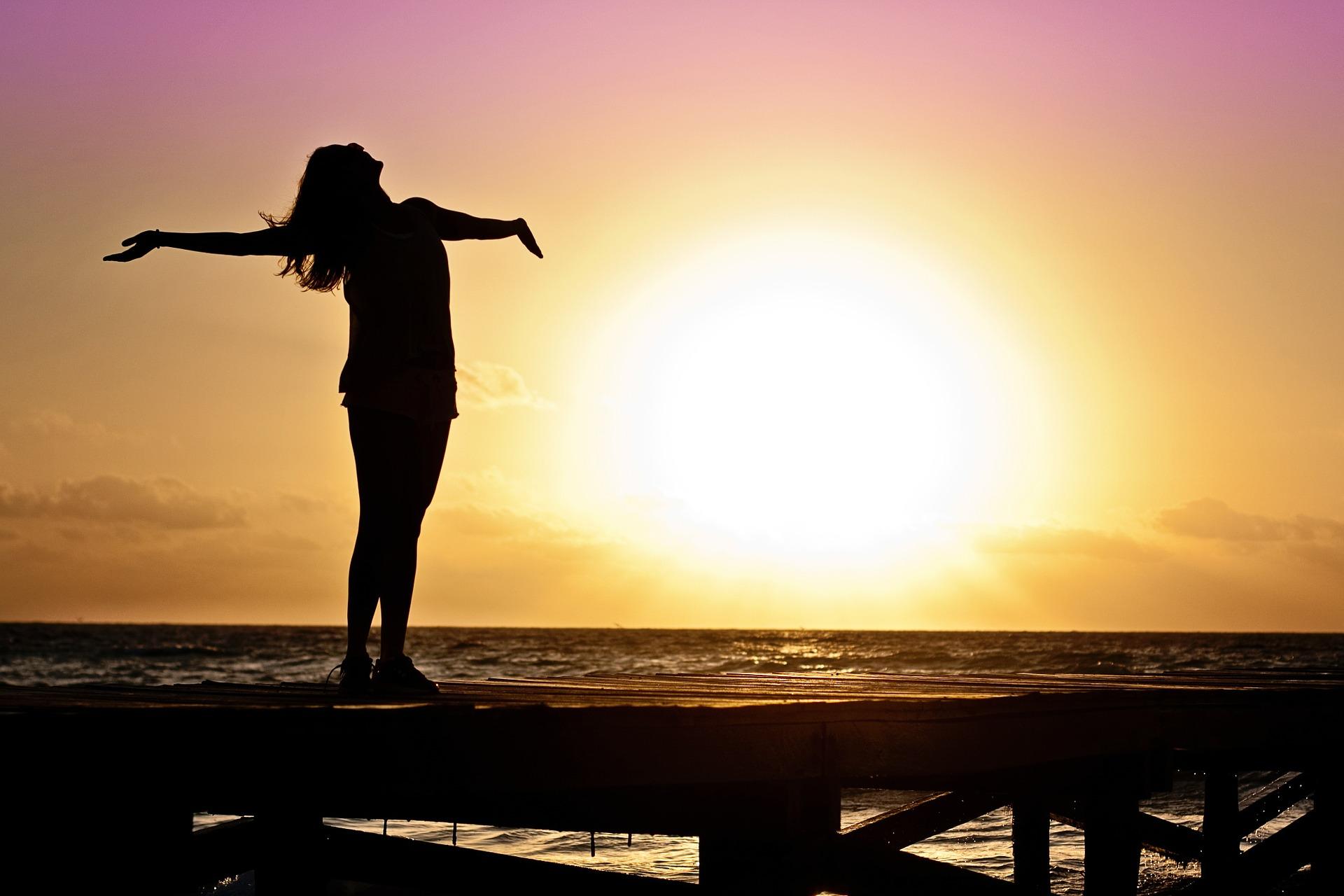 夕日と自由を感じる女性の画像