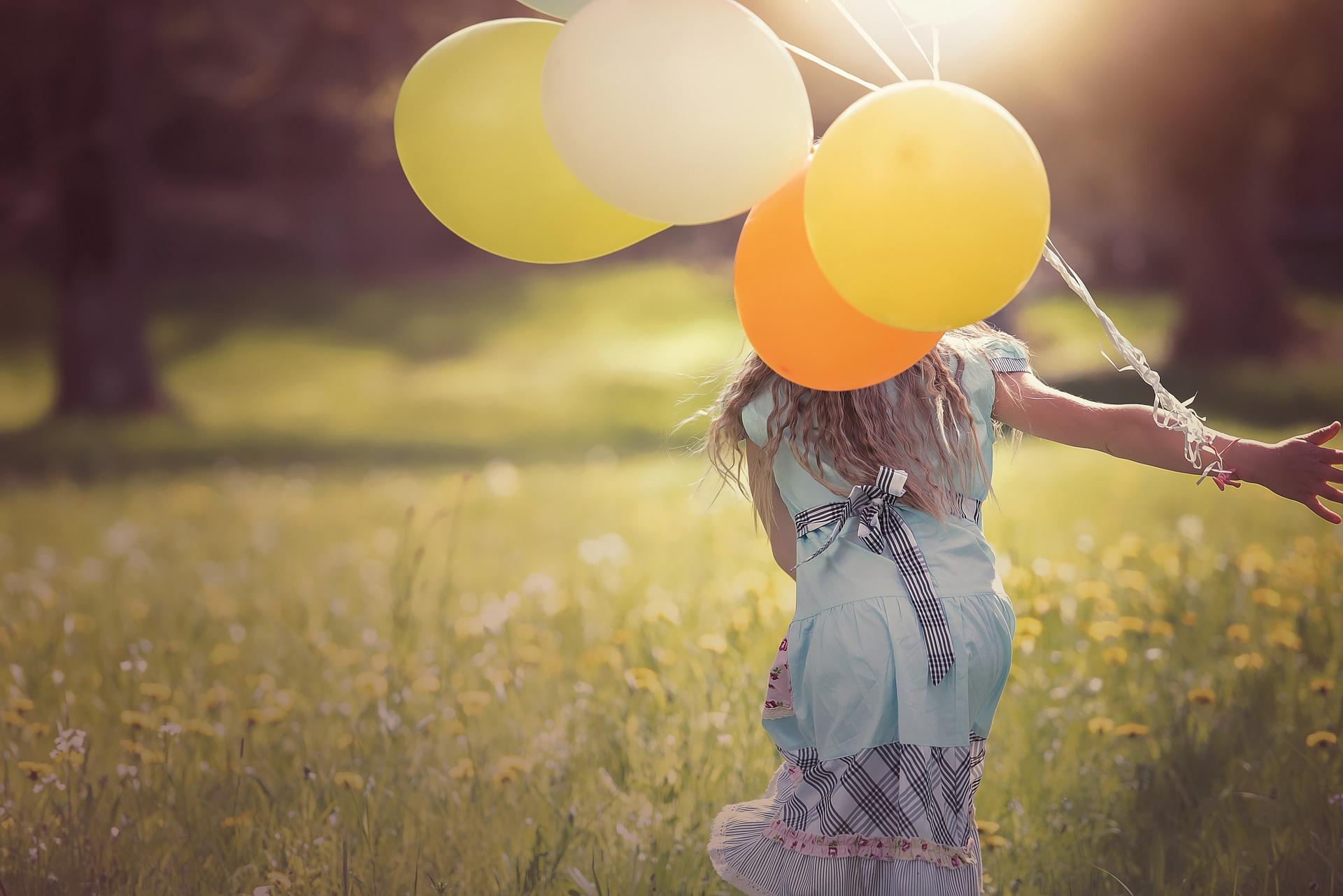 少女が風船を持っている画像