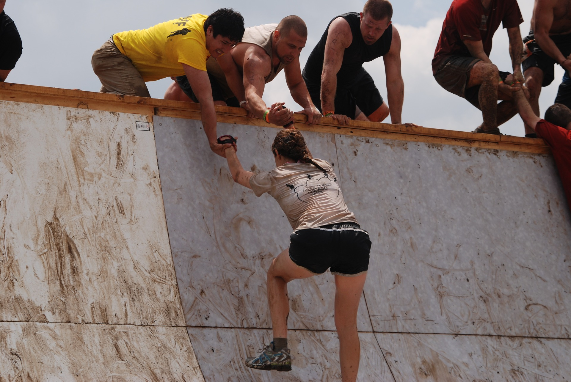 仲間に助けられて、壁を登る女性